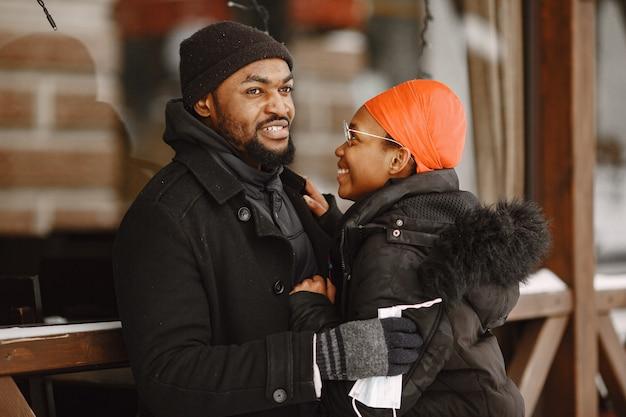 人々は外を歩きます。冬の日。アフリカのカップル。医療用マスクを持っている人。