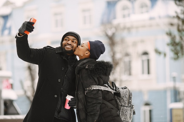 人々は外を歩きます。冬の日。コーヒーとアフリカのカップル。