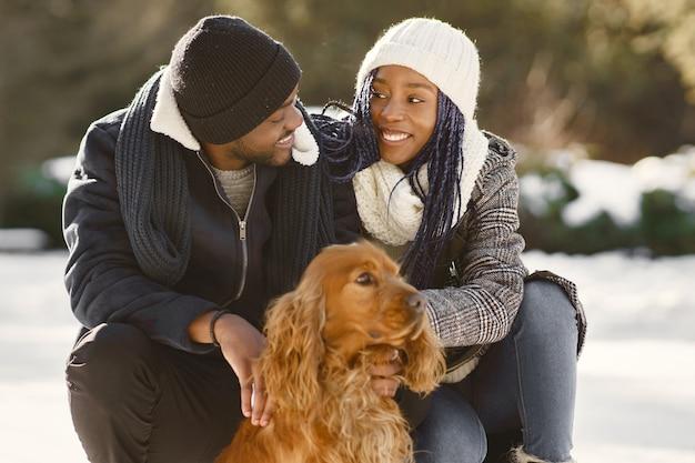 사람들은 밖으로 걸어갑니다. 겨울 날. 강아지와 함께 아프리카 커플입니다.