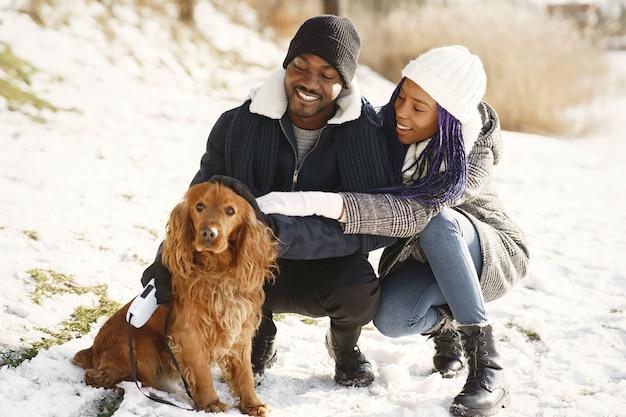 人々は外を歩きます。冬の日。犬とアフリカのカップル。