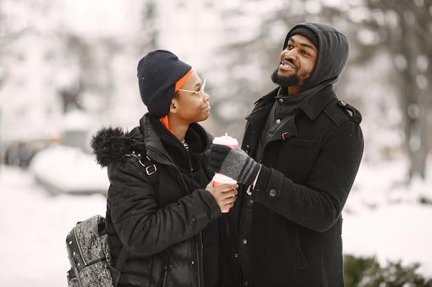 人々は外を歩きます。冬の日。アフリカのカップル。