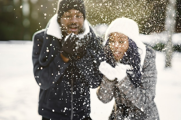 사람들은 밖으로 걸어갑니다. 겨울 날. 아프리카 커플