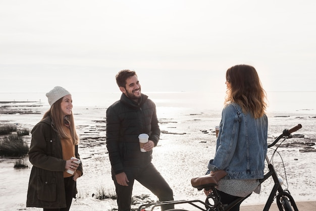 People in warm clothes talking on seashore