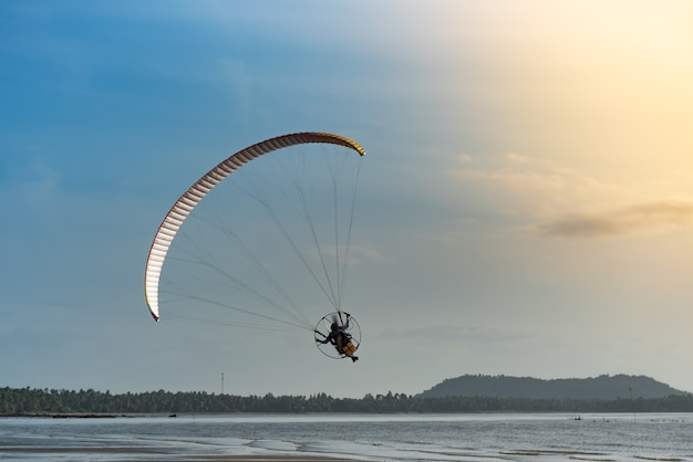 The people was playing a paramotor, flying above the beach with blue sky background