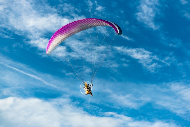 People was playing a paramotor flying on the blue sky background