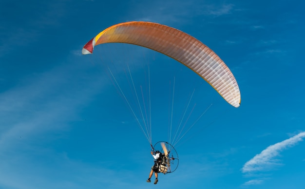 The people was playing a paramotor flying on bule sky background to recreation concept.