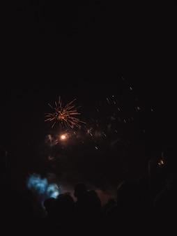 夜空に花火を見ている人