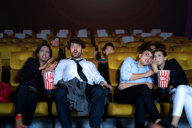 People watching movie feeling scary and frightening at movie theater