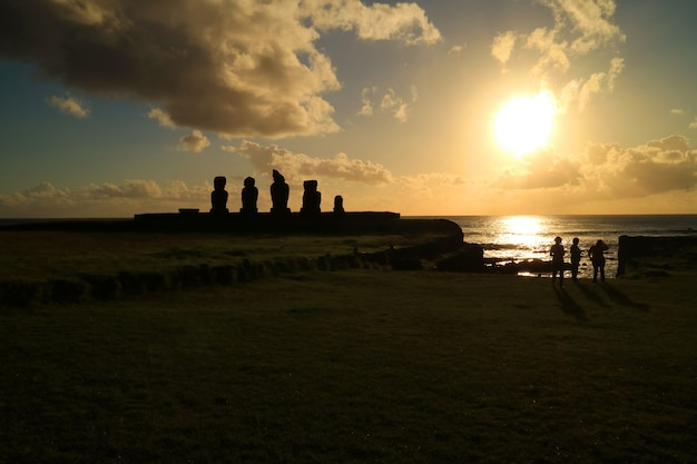 People watching sunset over pacific ocean at ahu tahai with moai statues, easter island, chile