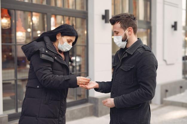 Люди, носящие защитную маску, стоят на улице, используя спиртовой гель