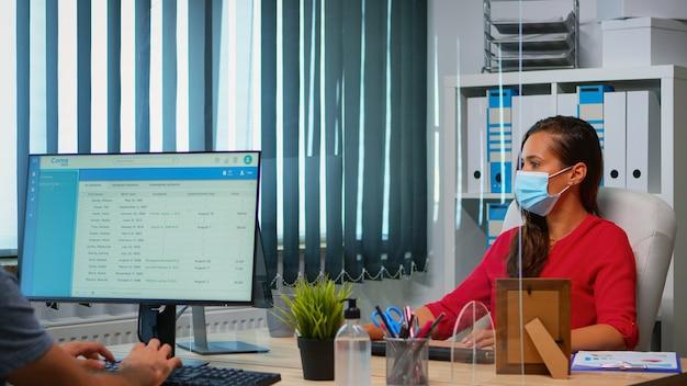 フェイスマスクを着用している人々は、新しい通常のオフィスで仕事に戻っています。個人的な企業のワークスペースで作業しているチームは、社会的距離を尊重してデスクトップを見て、コンピューターのキーボードで入力します。