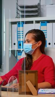 새로운 정상으로 사무실에서 다시 얼굴 마스크를 쓴 사람들. 사회적 거리를 존중하는 데스크탑을 바라보며 컴퓨터 키보드로 타이핑하는 개인 기업 회사의 작업 공간에서 일하는 팀.