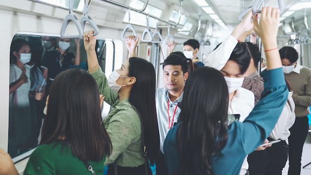 混雑した公共の地下鉄の電車でフェイスマスクを着用している人