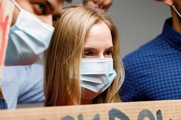 Люди в масках протестуют и держат плакаты