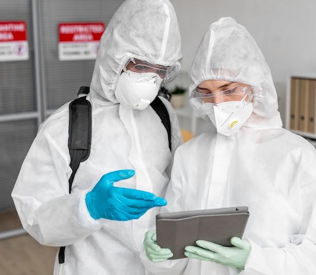 Persone che indossano dispositivi di protezione per disinfettare un'area pericolosa