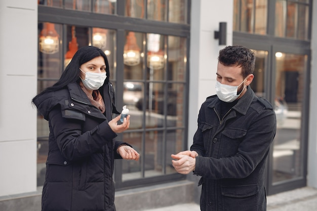 People wearing a protective mask standing on the street while using alcohol gel