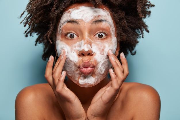 Concetto di persone, benessere, igiene e problemi di pelle. l'adorabile signora afroamericana tiene le labbra piegate, tocca le guance, ha la schiuma bianca sui volti, si lava con gel di bellezza, si sente rinfrescata, ha gli occhi spalancati