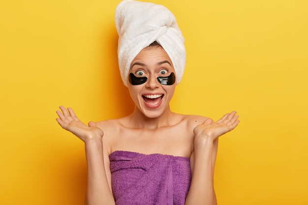 People, wellness and rejuvenation concept. positive european woman spreads palms sideways, makes beauty step for looking younger, wears cosmetic patches under eyes for reducing bags and puffiness