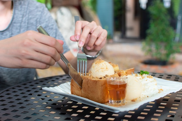 People were using their hands to cut the honey toast with a broach and a stainless steel knife placed in a plate with ice cream, honey, and whipped cream.