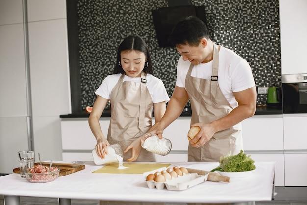 Persone mentre si preparano gli gnocchi. persone asiatiche in grembiuli.