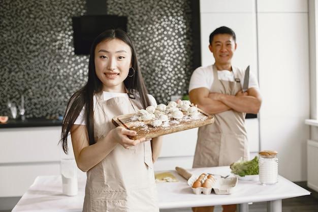만두를 준비하는 사람들. 앞치마를 입은 아시아 인.
