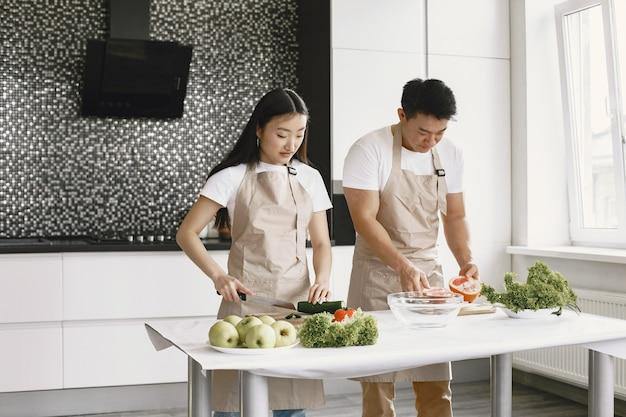 新鮮な野菜のサラダを作っている人。エプロンのアジア人。