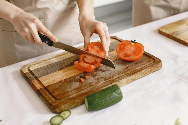 신선한 야채 음식 샐러드를 준비하는 동안 사람들. 앞치마를 입은 아시아 인.