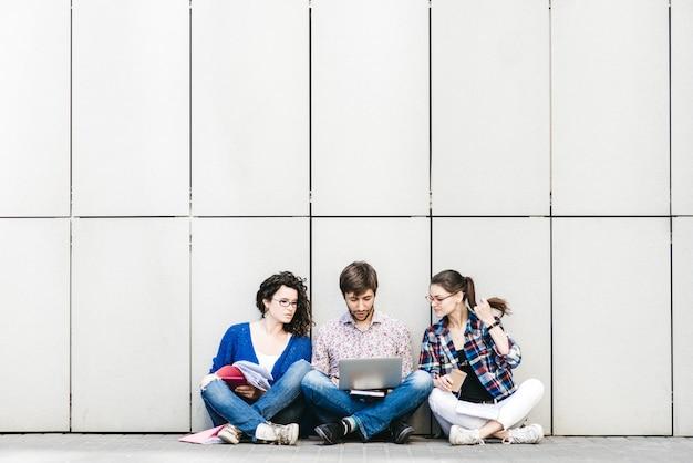 Люди с книгами и гаджетами сидят на полу у стены. концепция образования в социальных сетях.