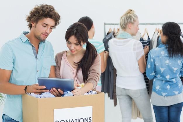 Люди с пожертвованием на одежду при использовании цифрового планшета