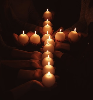 People with cross made of burning candles in darkness