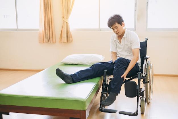 障害者はベッドから車椅子に移動します
