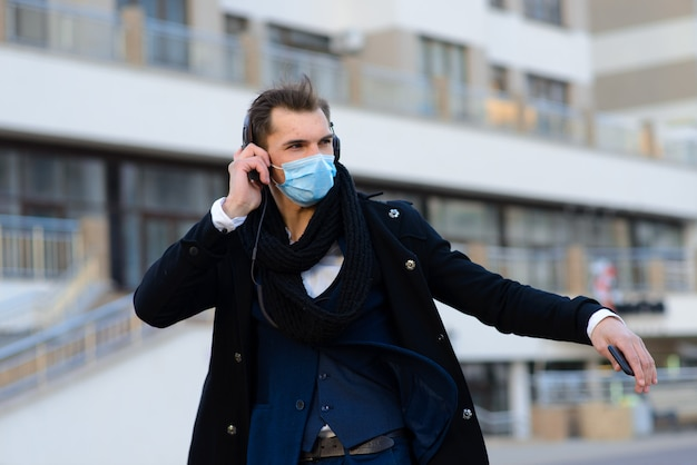 People with face mask. concept with copy space. portrait of adult man in quarantine of flu. photo on the street in the city