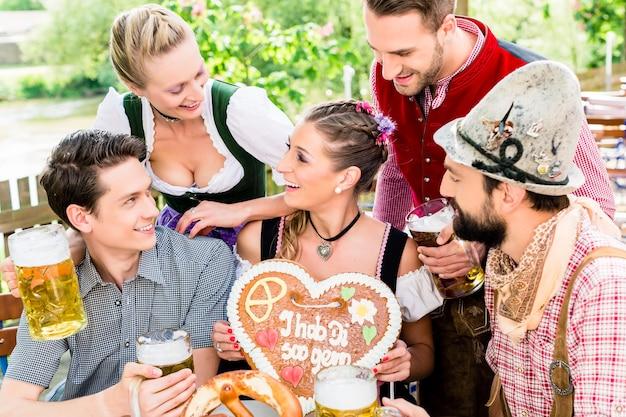 People with gingerbread heart in beer garden drinking beer in summer