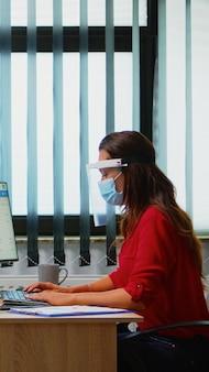 新しい通常のオフィスで働いているマスクとバイザーを持っている人は、レポートをチェックし、コンピューターで書いています。プレキシガラスを使用したcovidウイルスに対する保護ルールを尊重する現代の職場の同僚。