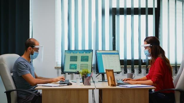 마스크와 바이저를 가진 사람들은 새로운 일반 사무실에서 보고서를 확인하고 컴퓨터에 글을 씁니다. 플렉시 유리를 사용하여 covid 바이러스에 대한 보호 규칙을 준수하는 현대 직장의 동료.