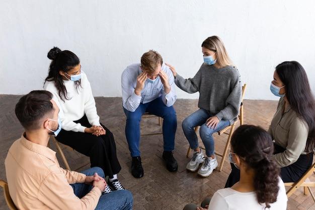 Persone con maschere mediche nella sessione di terapia di gruppo