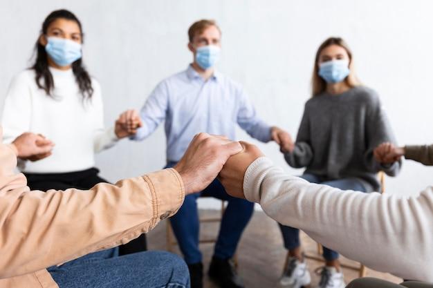 集団療法セッションで手をつないでいる医療用マスクを持つ人々