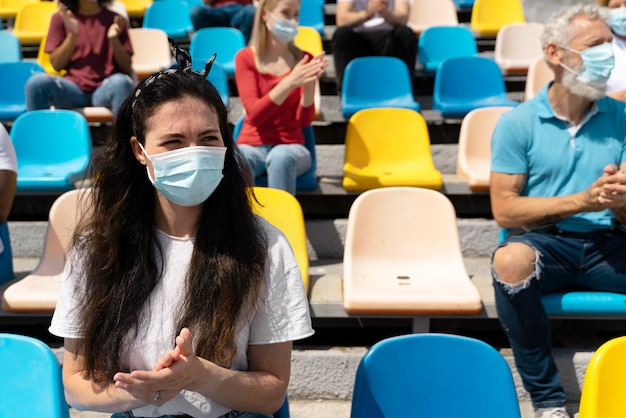 People with medical masks looking at a game