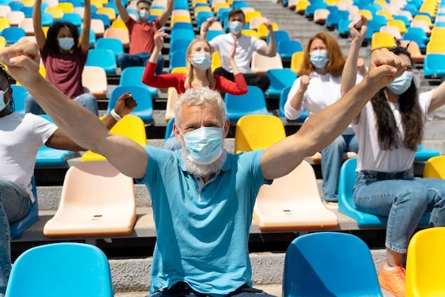 Persone con maschere mediche che guardano un gioco Foto Gratuite