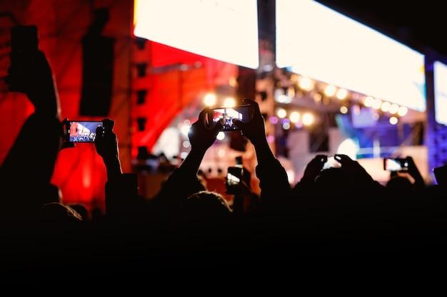 콘서트 이벤트를 촬영하는 손에 휴대 전화를 가진 사람들.