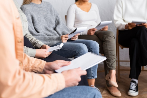 People with notebooks at a group therapy session