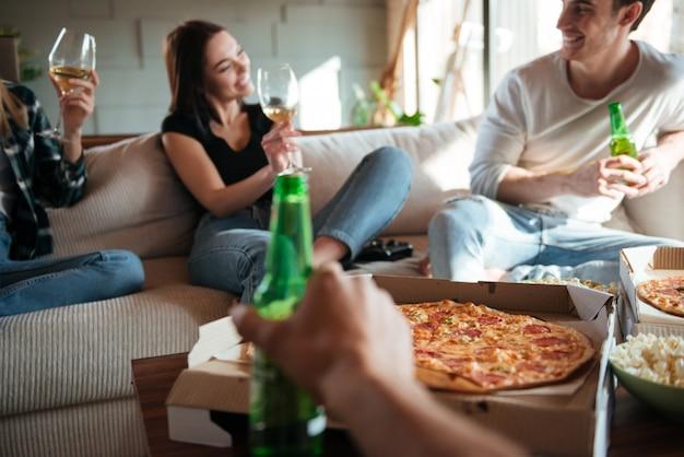 ピザ、ワイン、ビールを飲みながら話したり笑ったりしている人々