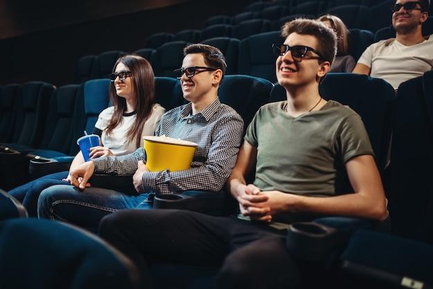 Люди с попкорном смотрят фильм в кино