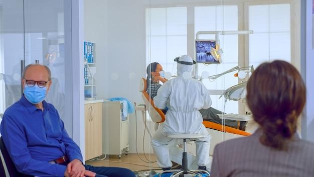 보호 마스크를 쓴 사람들은 치과 진료소에서 의사를 기다리는 동안 ppe 수트를 입고 백그라운드에서 일하는 동안 의사를 기다리고 있습니다. 새로운 일반 치과 방문의 개념