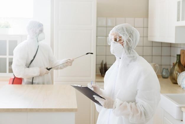 Людей в средствах защиты дезинфицируют с помощью краскопульта. обработка поверхности из-за коронавирусной болезни covid-19.