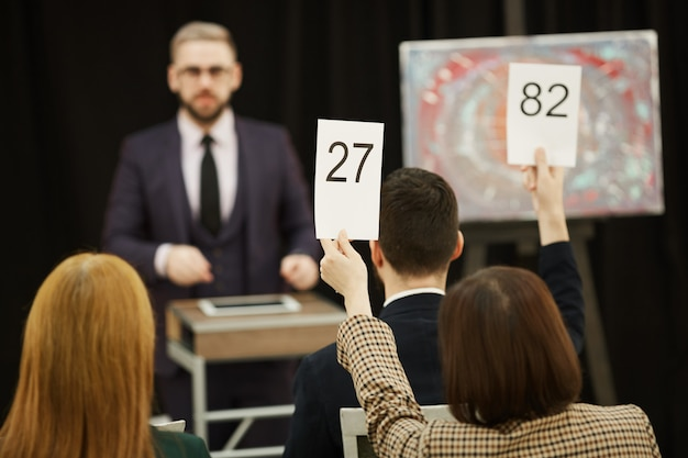People with signs at auction
