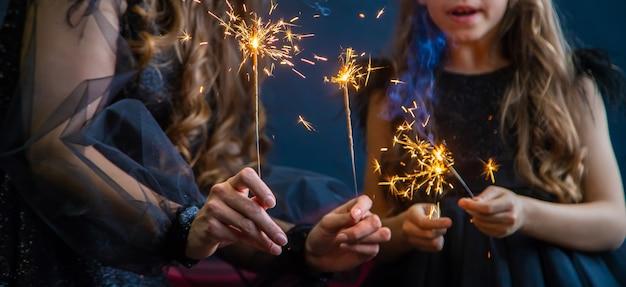 クリスマスの背景に線香花火を持つ人々。セレクティブフォーカス。ハッピー。