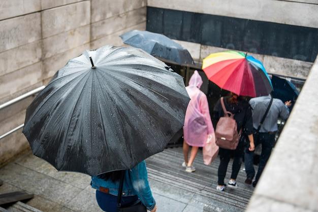 傘を持った人が地下道に降りてきます。雨の日の街並み。雨滴の傘。悪天候。