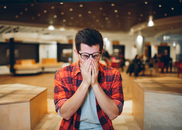 People and work concept - tired man with eyeglasses in office