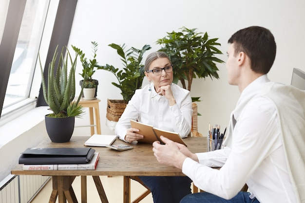 People, work, employment, occupation and profession concept. experienced serious gray haired mature female human resources specialist holding notebook while conducting job interview with young man